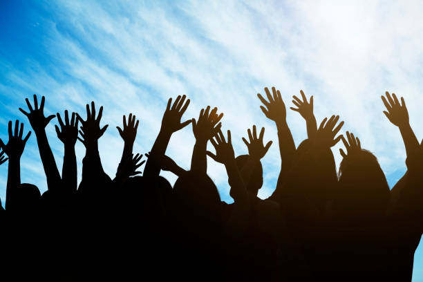 Group of people raising their hands against a blue sky stock photo