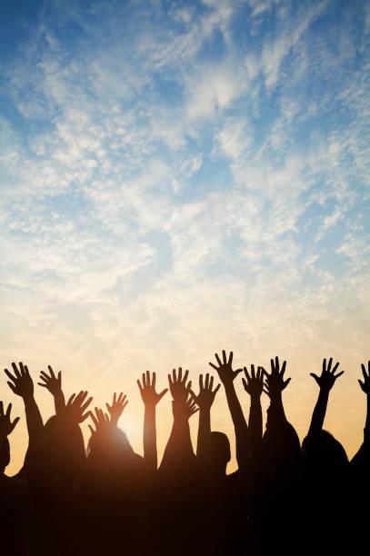 gruppe von menschen, die ihre hände gegen einen sonnenuntergang heben - arme hoch stock-fotos und bilder