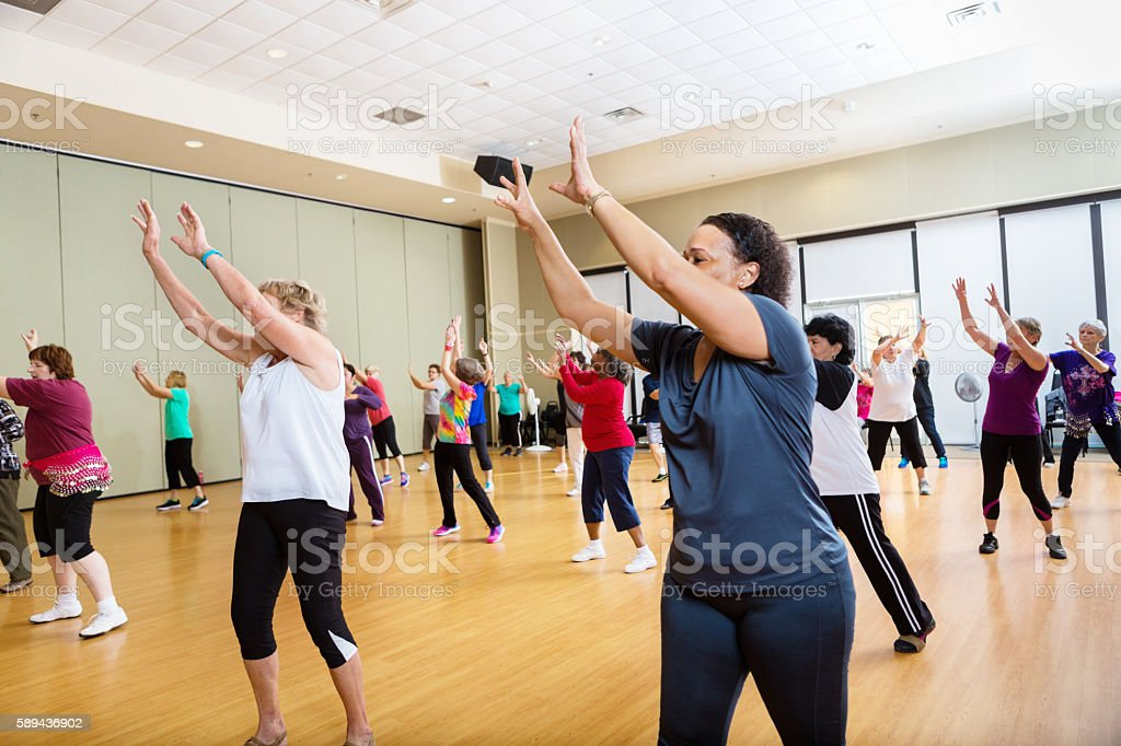 Group of people reaching up in dance class stock photo