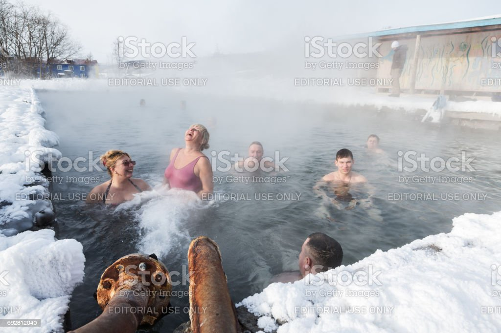 Group of people relaxing in geothermal spa in hot spring pool with natural thermal mineral water having balneological properties stock photo