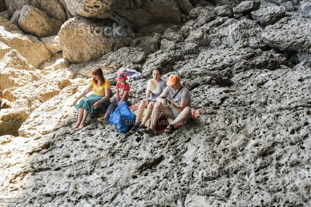 A group of people resting on a rock. royalty-free stock photo
