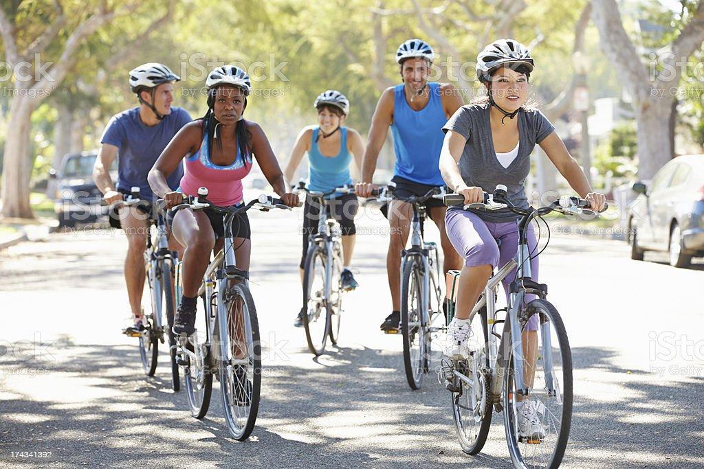Group of people riding bikes down a suburban street stock photo