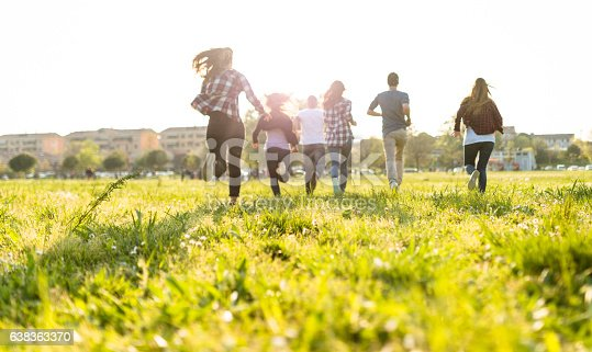 istock Group of people running on the park at dusk 638363370
