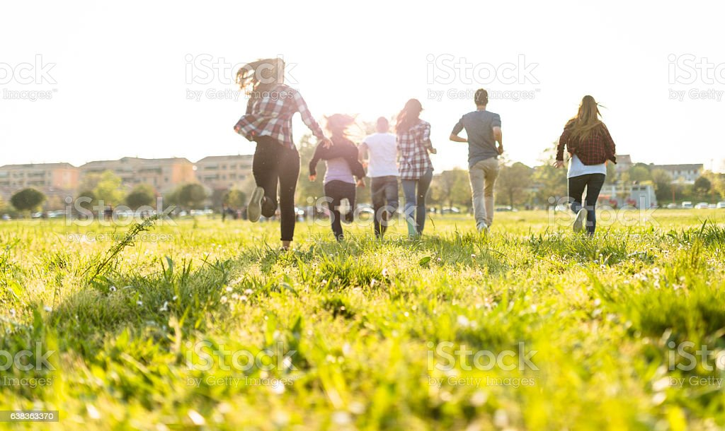 Group of people running on the park at dusk stock photo