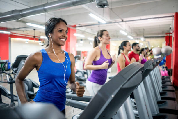 Group of people running on the treadmills at the gym stock photo