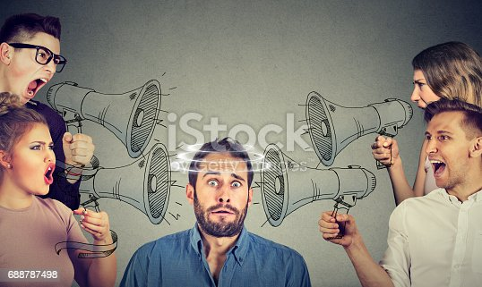 Group of people screaming in megaphones at scared guy