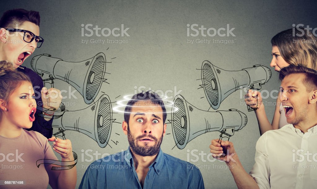 Group of people screaming in megaphones at scared guy stock photo