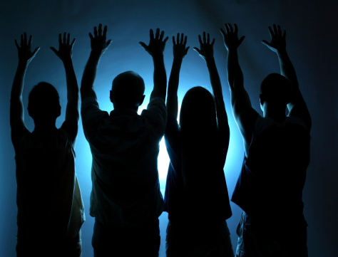 Four people offering praise or worship.   Spirituality. Blue light background.  Cult, religion, followers. Silhouette.