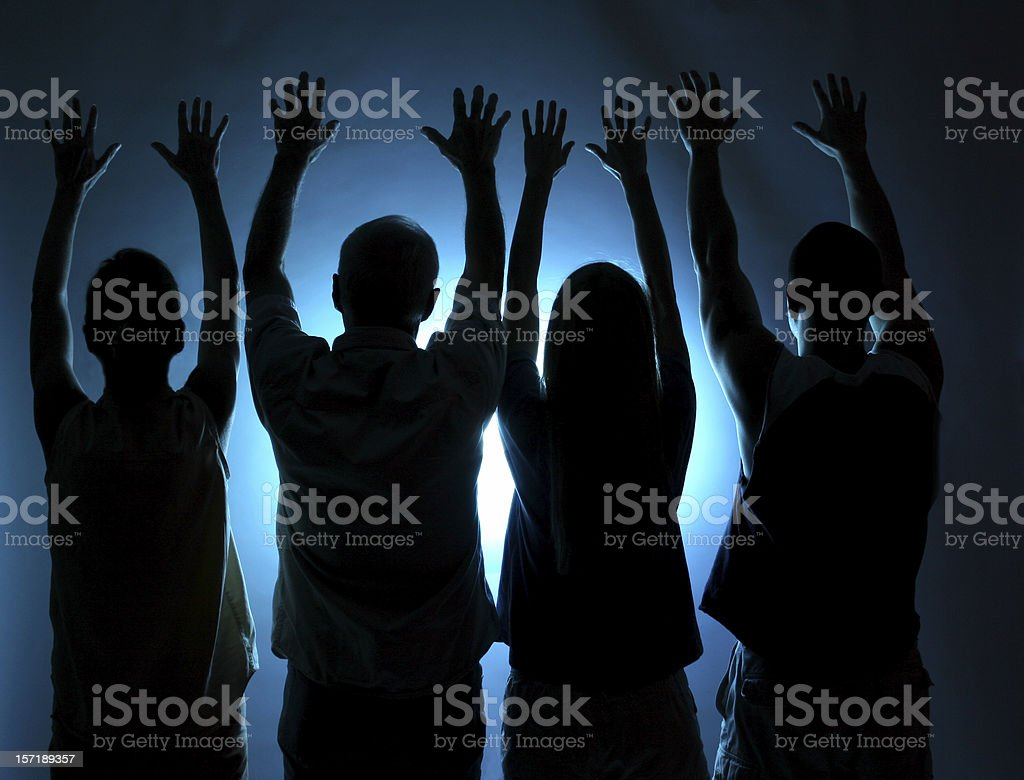 Group of people silhouette. Arms raised in praise. Blue light. stock photo
