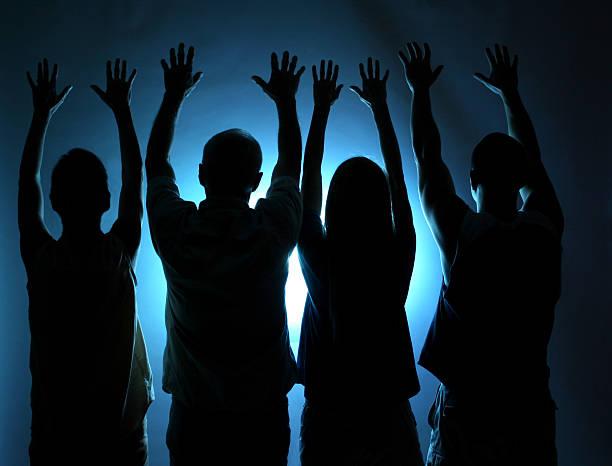 grupo de pessoas silhueta. braços levantados em apreço. luz azul. - seitas imagens e fotografias de stock