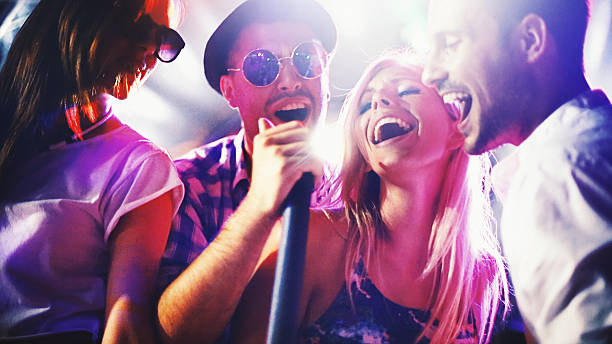 group of people singing karaoke. - singing stock photos and pictures