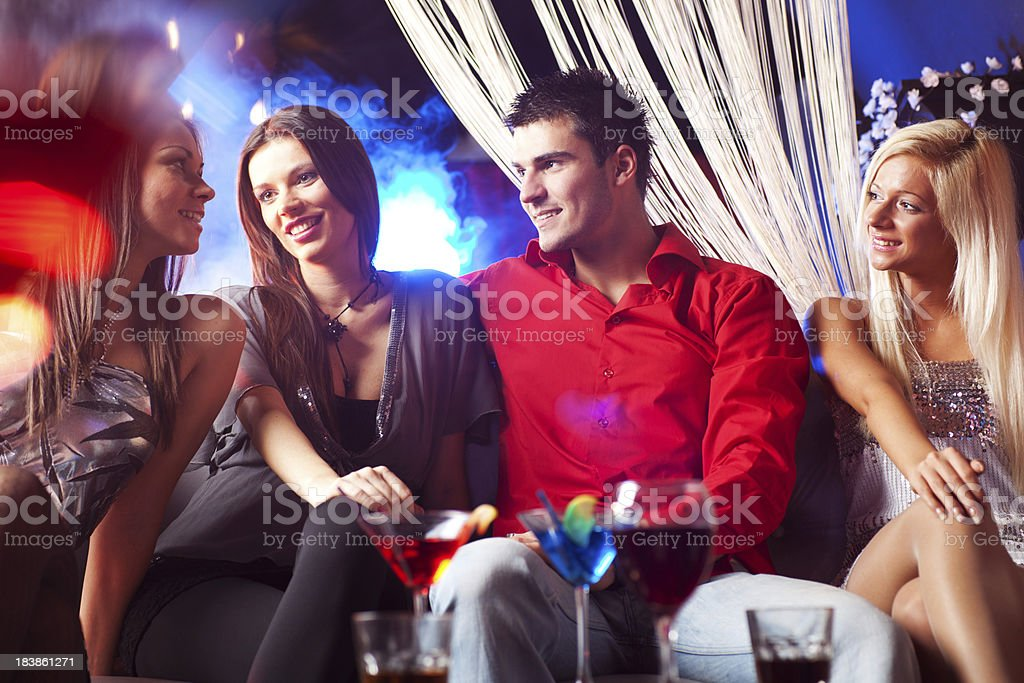 Group of people sitting at disco club and talking royalty-free stock photo