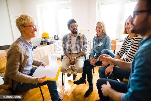 istock Group of people sitting in a circle on group therapy. Looking at their therapist and listening ti her story. 1039533386