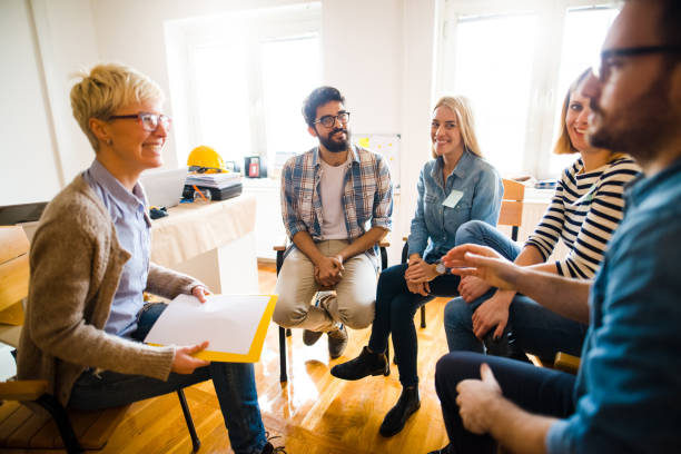 Group of people sitting in a circle on group therapy. Looking at their therapist and listening ti her story. stock photo
