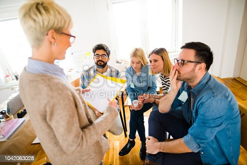 istock Group of people sitting in a circle on group therapy. Looking at their therapist and listening ti her story. 1042063028