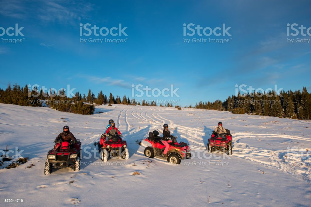Group of people sitting on off-road quad bikes in the the mountains in winter evening stock photo