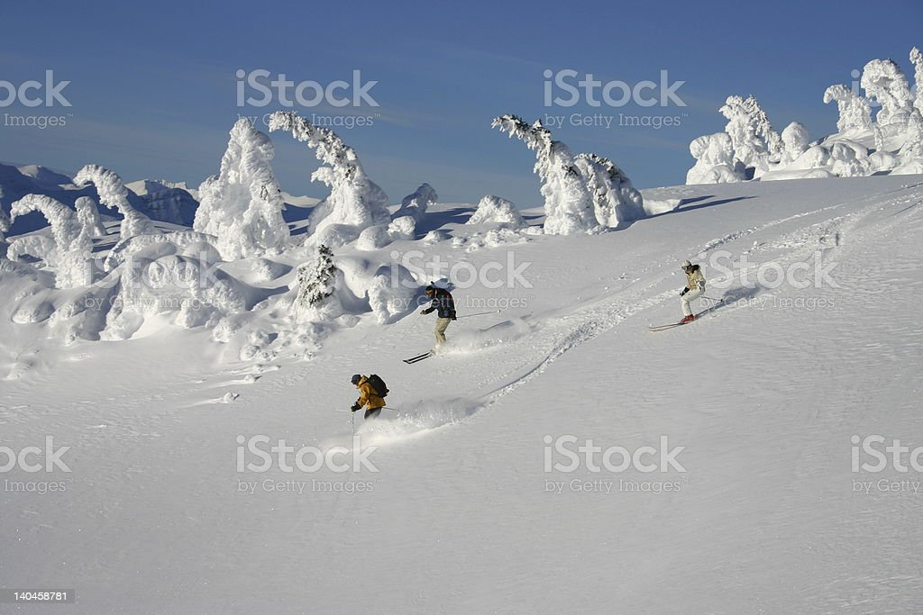 A group of people skiing down a slight slope stock photo