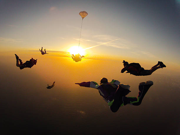 Group of people skydiving at sunset