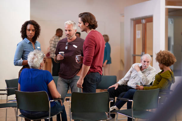 Group Of People Socializing After Meeting In Community Center Group Of People Socializing After Meeting In Community Center community center stock pictures, royalty-free photos & images