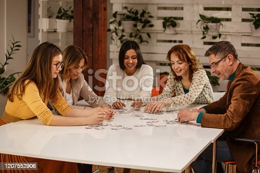 Group of happy people solving a puzzle in an office environment.