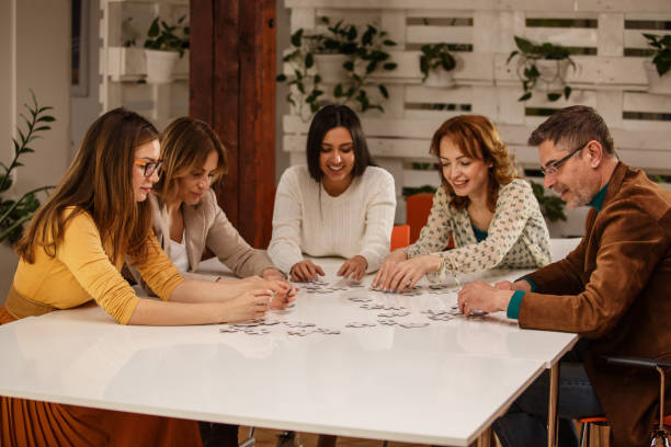 Group of people solving a puzzle stock photo
