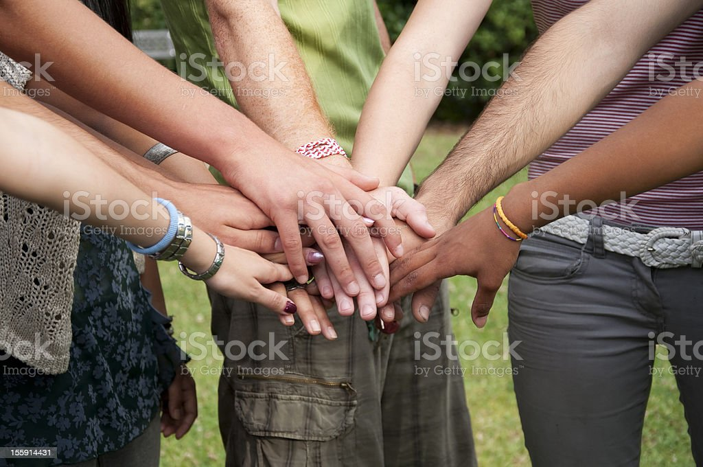 Group of people stack hands outdoors stock photo