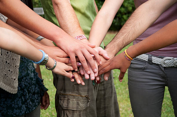 Group of people stack hands outdoors The arms of several people are stacked in the center of the image.  The arm flesh takes up the top half of the image, and three of the people's legs take up the bottom half of the image.  The skin color ranges from white to medium-brown.  There is green grass and trees peeking through in the background. teenagers only stock pictures, royalty-free photos & images