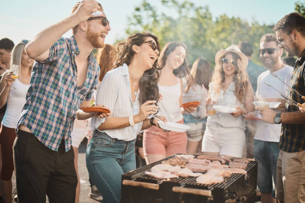 Group of people standing around grill. stock photo