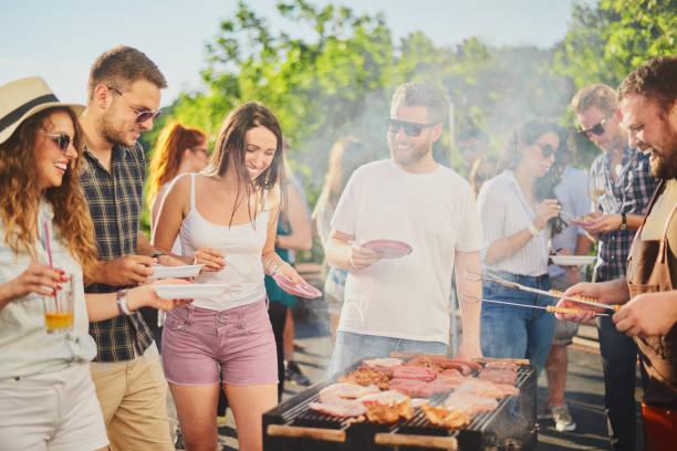 grupa ludzi stojących wokół grilla. - barbecue zdjęcia i obrazy z banku zdjęć