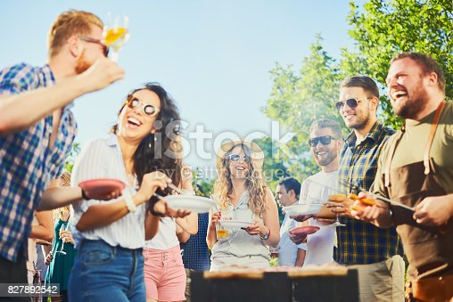 istock Group of people standing at barbecue party 827892542