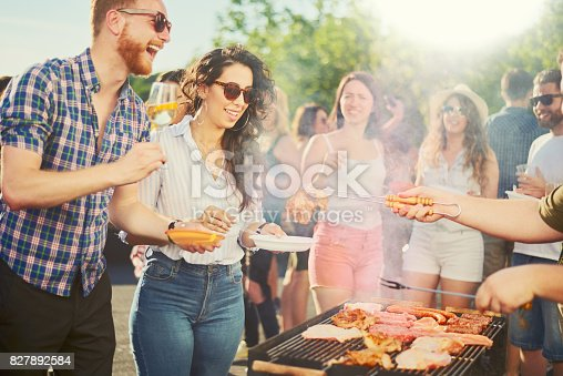 istock Group of people standing at barbecue party 827892584