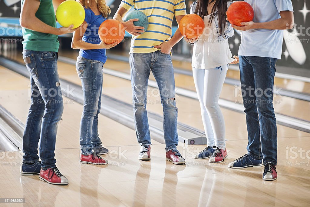 Group of people standing in bowling alley stock photo