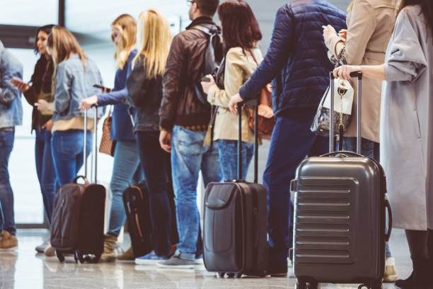 group of people standing in queue at boarding gate - aeroplane ticket stock photos and pictures