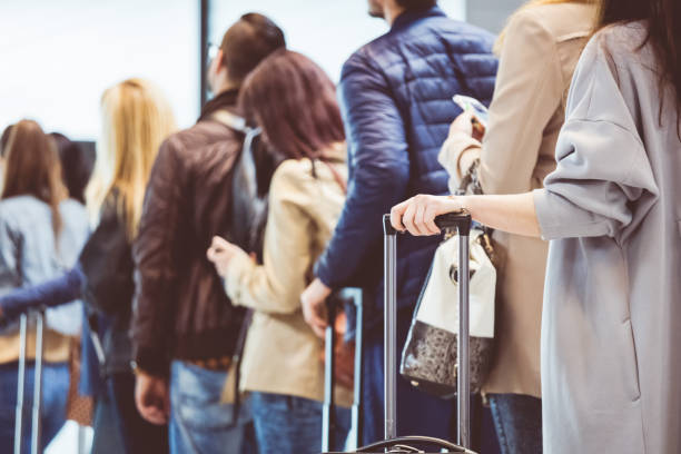 group of people standing in queue at boarding gate - airport check in counter stock pictures, royalty-free photos & images