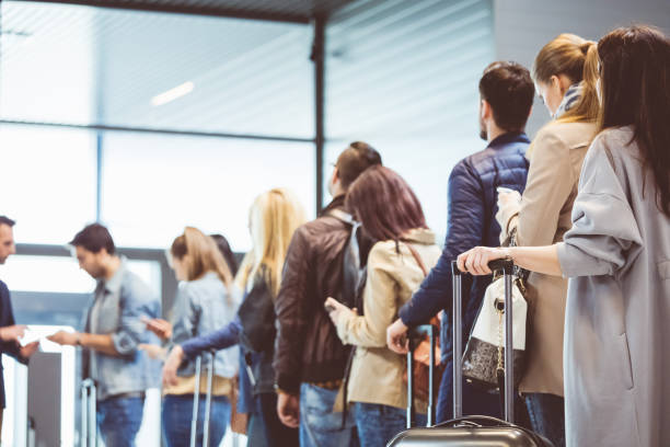 Group of people standing in queue at boarding gate Shot of queue of passengers waiting at boarding gate at airport. Group of people standing in queue to board airplane. passenger stock pictures, royalty-free photos & images