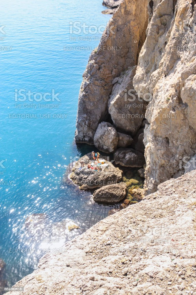 A group of people sunbathing on a rock under a rock. royalty-free stock photo