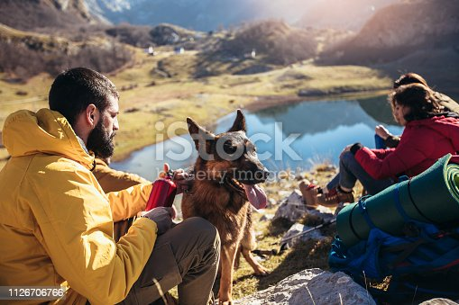 Group of people taking a break, relaxing during a hike.