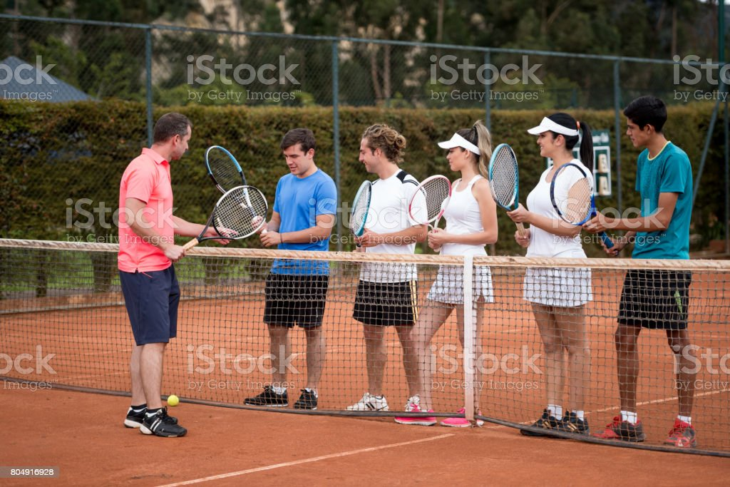 Group of people taking tennis lessons stock photo