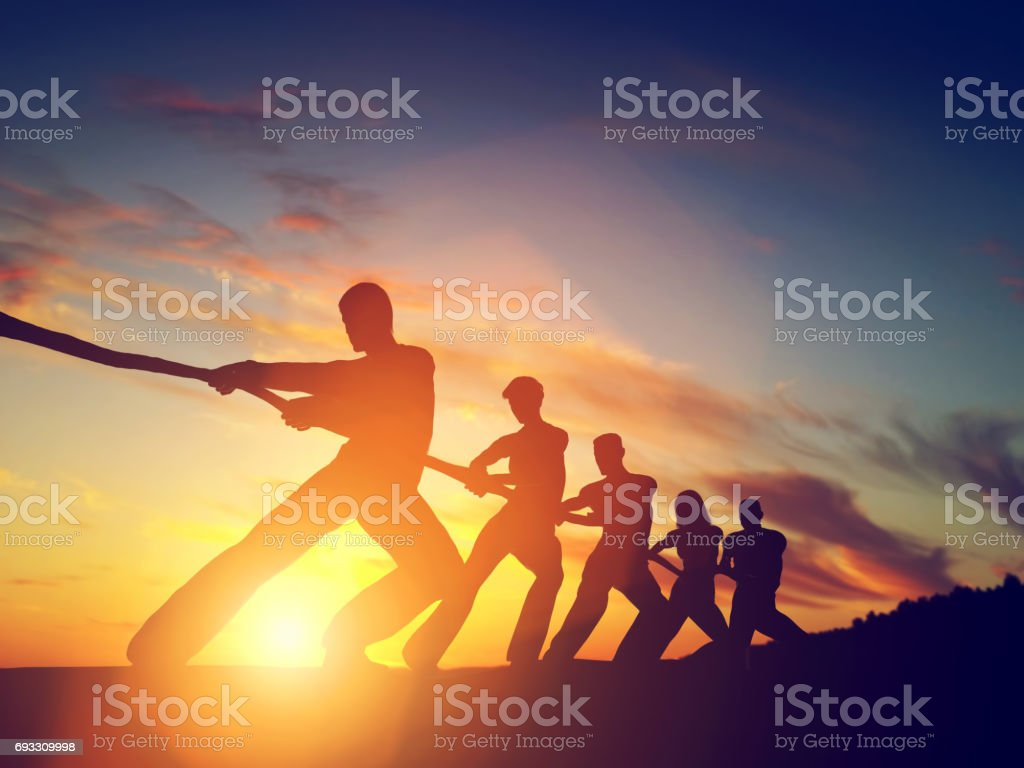 Group of people, team pulling line, playing tug of war. stock photo