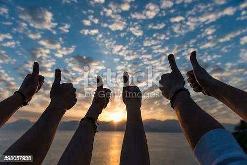 istock Group of people thumbs up at sunset 598057938