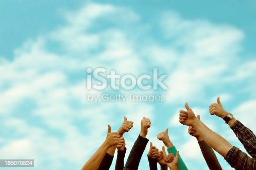 Group of 11 people giving a thumbs up.  Only the people's arms are visible in front of background of a light blue sky with intermittent white and diaphanous gray clouds.