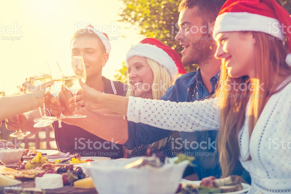 Group of people toasting with Santa hats. stock photo