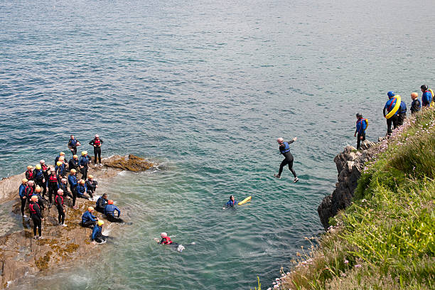 group of people tombstoning in newquay - cornwall stock pictures, royalty-free photos & images