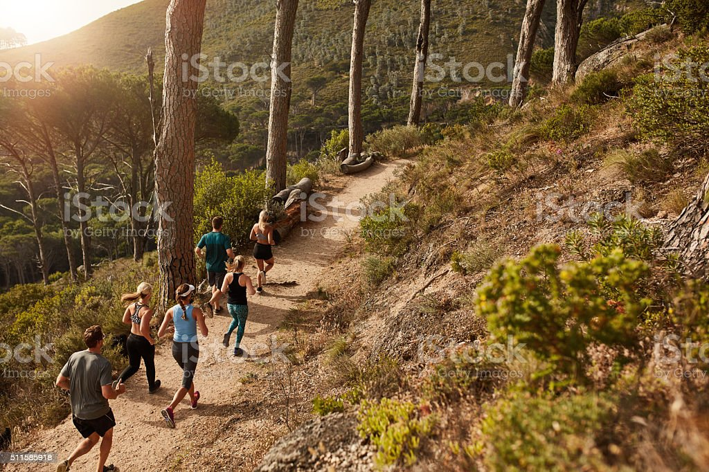 Group of people trail running on a mountain path stock photo