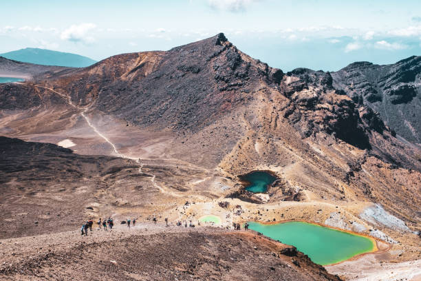 A group of people trekking in Beautiful Landscape of Tongariro Crossing track on a beautiful day. stock photo