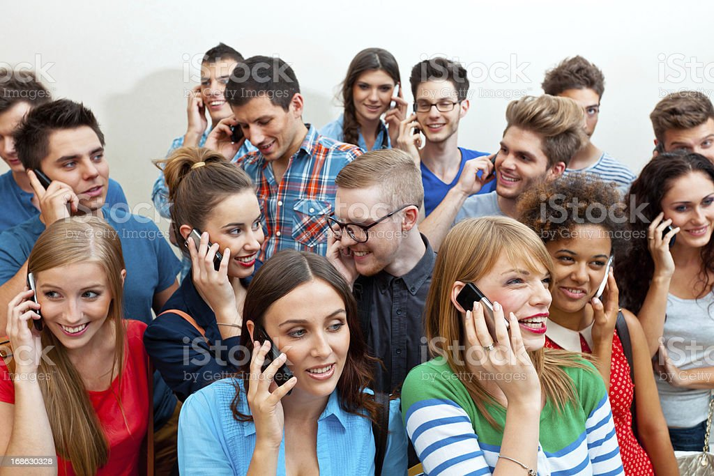Group of people using mobile phone Large group of young adult people using mobile phone. High angle view. 20-24 Years Stock Photo