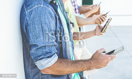 istock Group of people using smartphones while watching videos outdoor - Friends having fun with technology trends - Youth, tech and friendship concept - Focus on first man hand mobile phone 920038244