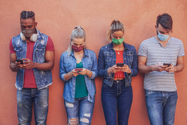 grupo de pessoas que usam seus smartphones em covid 19 vezes protegido com máscara facial - amigos verificando notícias online enquanto estão ao lado da parede e segurando celulares - vida de estudante - fotografias e filmes do acervo