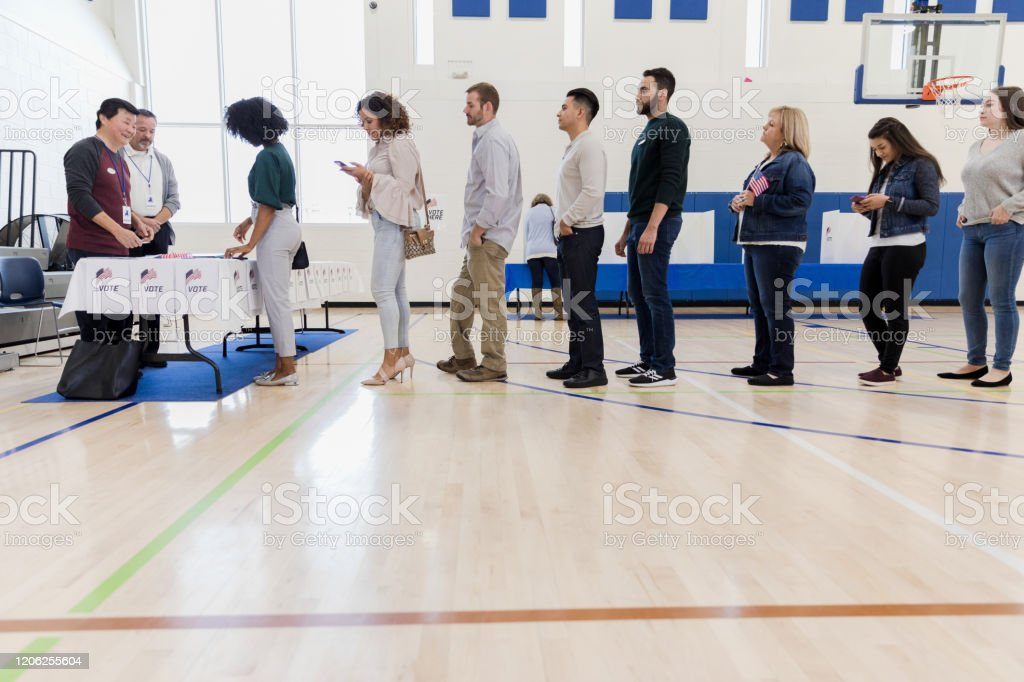 Group of people wait in long line in polling place A long line of people wait to vote in poling place. A few of the people pass the time by using their smartphones. Active Seniors Stock Photo