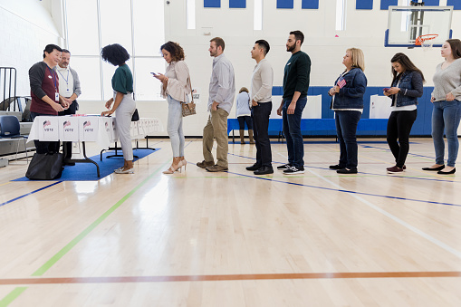 Group Of People Wait In Long Line In Polling Place Stock Photo - Download Image Now